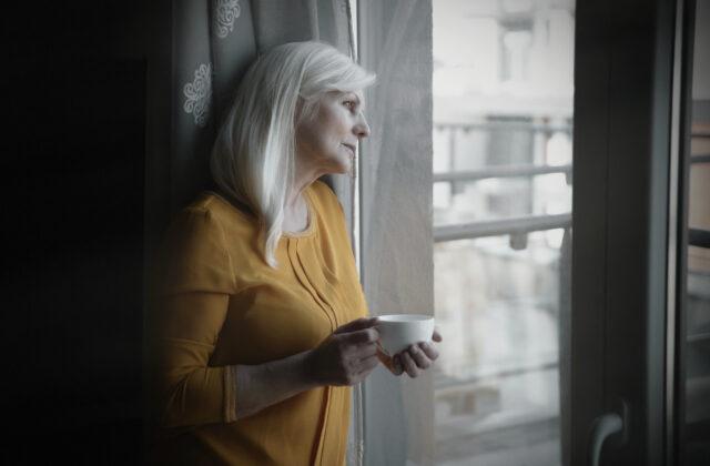 Starsza smutna kobieta stojąca przy oknie z filiżanką w ręce