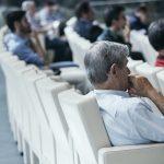 Mężczyźni siedzący na sali konferencyjnej słuchający wykładu