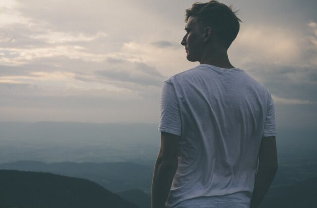 Młody mężczyzna stojący tyłem na szczycie wzgórza i patrzący w dal