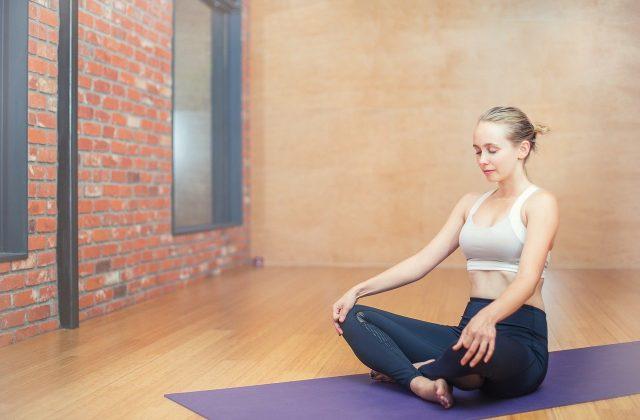 młoda kobieta siedząca i medytująca na macie ze skrzyżowanymi nogami